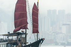 Hong Kong junk. A Hong Kong junk with red canvas sailing in front of the faded silhouette of the highrises of Hongkong Royalty Free Stock Photos