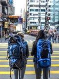 HONG KONG KINA - December 9 2016: Ung flicka två med ryggsäcken över övergångsstället på vägen med stadsbakgrund Hong Kong arkivfoton