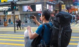 HONG KONG KINA - December 9 2016: Ung man med bagagepåsen på stadsgatan med översikten i Hong Kong som tar fotoet med den smarta  royaltyfri bild
