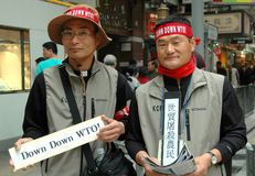 Hong Kong: Koreans Protesting WTO Meeting. Two Korean protesters holding signs in both English and Chinese demonstrate on Nathan Road against a World Trade Stock Image
