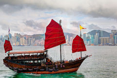Hong Kong Landscape: Chinese Sailboat on Victoria Harbor. HDR rendering of a typical Chinese junk ship with red sails on Victoria Harbor in Tsim Sha Tsui, Hong Royalty Free Stock Photo