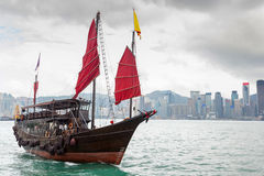 Hong Kong Landscape: Chinese Sailboat on Victoria Harbor. A Chinese junk ship with red sails on Victoria Harbor in Tsim Sha Tsui, Kowloon, with Hong Kong's Royalty Free Stock Photos