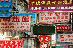 Hong Kong: A Mélange of Signs. A mélange of signs advertising hotels, karaoke clubs, stores, and businesses hang from bamboo poles over a street in the Mong Stock Image