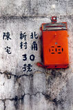 Hong Kong mailbox. Shot of an orange hong kong mailbox against a weathered concrete wall with my address written in chinese characters royalty free stock photo