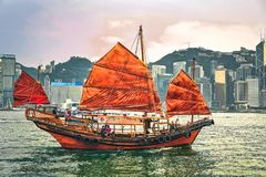 Junk boat at Victoria Harbour in Hong Kong at sunset. View from Kowloon on HK Island. Hong Kong, Hong Kong - March 6, 2016: Junk boat at Victoria Harbour in Hong stock photo