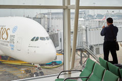 Airbus A380. HONG KONG - MARCH 09, 2015: a man taking photo of docked Airbus A380. The Airbus A380 is a double-deck, wide-body, four-engine jet airliner Royalty Free Stock Image