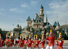Hong Kong: Marching Band at Disneyland. Colourfully dressed brass marching band performs a concert in front of the fabled Sleeping Beauty Castle at Hong Kong's Stock Photo