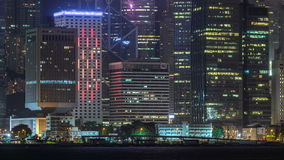 Hong Kong night view of skyline with reflections at victoria harbor timelapse. Hong Kong night view of skyline with reflections of towers at victoria harbor stock video footage