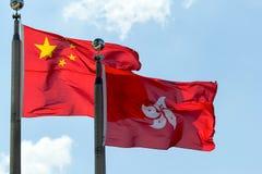 Hong Kong och Kina flaggor sid - förbi - sidan Arkivbild