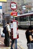 Hong Kong-October 7, 2016: Väntande på buss för folk på en hållplats på vägrenen Royaltyfri Bild