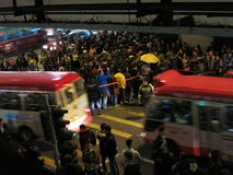 Hong Kong Protesters on Street as Buses Drive By. HONG KONG, DEC. 6, 2014: Occupy Mongkok protesters fill the sidewalks and part of the street where buses are royalty free stock photo