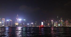 Hong Kong red boat. Hong Kong, China - December 1, 2016: City skyline with illuminated skyscrapers and red-sail junk boat Aqua Luna, sailing at night for stock footage