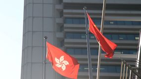Flags of China and Hong Kong waving in the wind. Hong Kong regional flag and China flag waving in the wind over modern building background. Flag of the People`s stock video footage