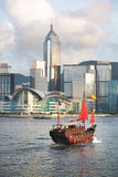 Hong Kong's traditional old junk ship sailing. Sunset view of a traditional, junk ship with wind sails shot against modern cityscape of Hong Kong island and Stock Image