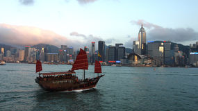 Hong Kong's traditional old junk ship sailing. Sunset view of a traditional, junk ship with wind sails shot against modern cityscape of Hong Kong island and Royalty Free Stock Image