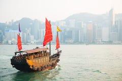 Hong Kong - September 23, 2016 :Chinese wooden sailing ship with. Red sails in Victoria harbor at Hong Kong Island, landmark Stock Photos