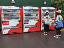 Young asian women buy coca cola drinks in Hong Kong. HONG KONG - SEPTEMBER 2017: Two unidentified young women buy Coca Cola drinks near Hong Kong Disneyland. The Stock Image