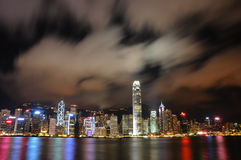 Hong Kong Skyline. A night capture of the famous Hong Kong skyline from Victoria Harbor. Drifting clouds forms an interesting pattern with the long exposure Royalty Free Stock Image