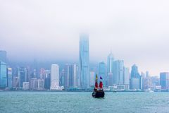 Hong Kong skyline. And boat on a cloudy rainy day Royalty Free Stock Image