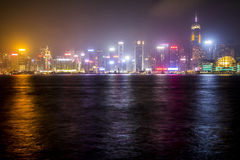 Hong Kong - 2015: Skyline of Hong Kong island at night. The photo shows the skyline of Hong Kong island at night. City lights and neons are reflected over the Stock Photo
