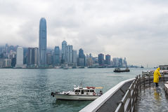 Hong Kong skyline. Hong Kong - Hongkong skyline with boats and street sweeper during rainy day. View from Kowloon quay Stock Photography
