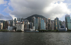 Hong Kong Skyline. Hong Kong - July 2016 Hong Kong skyline with tall buildings lining the coast and Victoria Peak in the background stock photography