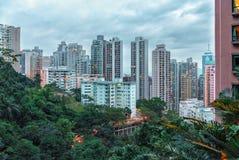 Hong Kong-stads privé woonhigh-rise gebouwen in de avond Toneel bewolkte cityscape met groene bomen en wolkenkrabbers royalty-vrije stock foto's
