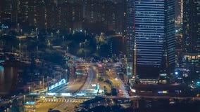Hong Kong-stadshorizon timelapse bij nacht met Victoria Harbor en wolkenkrabbers door lichten over bekeken die water wordt verlic stock videobeelden