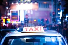 Hong Kong-Stadtbild mit Taxiauto an der Nachtstadtstraße Lizenzfreie Stockbilder