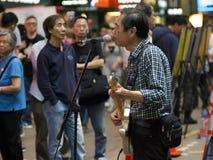 Hong Kong stary człowiek bawić się gitarę na ulicie obraz stock