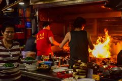 Hong Kong street kitchen. It was taken at night in sham shui po in Hong Kong. cooks are frying chinese food with fierce heat. The kitchen is busy and open on the royalty free stock photo