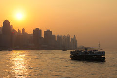 Hong Kong Sunset. A sunset over Kowloon in Hong Kong with a Star Ferry in the foreground Stock Photo