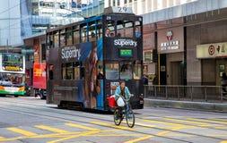 Hong Kong tramway. A bicyclist riding along the  tramway on  Central District  Hong Kong Island Royalty Free Stock Photo