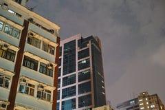 HONG KONG. Urban districts of Hong Kong at night. Skyscrapers, heavy dilapidated houses, all mixed up stock photo