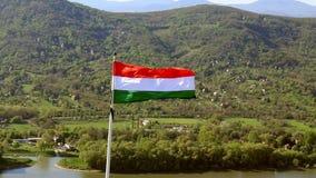 Hongaarse vlag die in de wind met platteland op de achtergrond golven stock footage