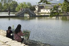 Hongcun bridge and artists. Artists painting the famous bridge at Hongcun, Anhui, China Stock Photo