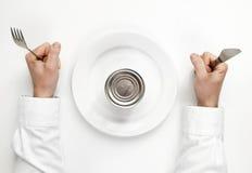 Hongerconcept. ongeopende tindoos met menselijke handen die vork a houden royalty-vrije stock afbeeldingen