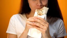 Hongerig meisje die shawarma eten, die van heerlijk maar ongezond voedsel, verslaving genieten stock fotografie