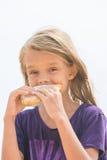 Hongerig meisje met een eetlust voor het bijten van een heerlijke pastei royalty-vrije stock foto