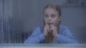 Hongerig weeskind die stuk van brood eten, sociale onzekerheid, kinderenrechten stock videobeelden