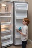 Hongerig weinig jongen die lege koelkast onderzoeken Stock Afbeeldingen