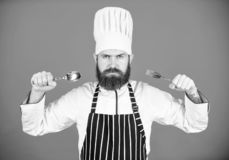 Hongerige chef-kok klaar om voedsel te proberen Tijd om smaak te proberen De greeplepel en vork van het chef-kok ernstige strikte royalty-vrije stock afbeeldingen