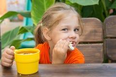 Hongerige grappige meisje het bijten broodje en het drinken thee Stock Afbeelding
