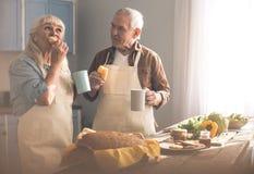 Hongerige hogere man en vrouw die gebakje in kokruimte eten stock foto