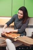 Hongerige meisjeszitting op keuken die diner van Italiaanse pizza hebben stock afbeeldingen