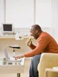 Hongerige mens die een sandwich eet en op laptop typt stock afbeeldingen