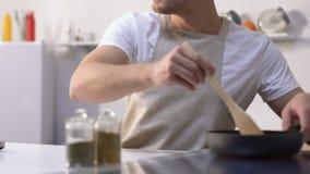 Hongerige mens die op videorecept op laptop letten, die amateur het bewegen ingrediënten koken stock videobeelden
