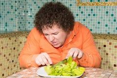 Hongerige mens en een plaat van salade Dieet en een gezonde levensstijl stock fotografie