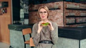 Hongerige toevallige mooie vrouw die etend smakelijke hamburger bij restaurant die positieve emotie hebben stellen stock video