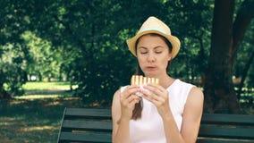 Hongerige vrouw die sandwich in park eten Toerist die lunch in openbaar park hebben die de zomer van zonnige dag genieten stock video